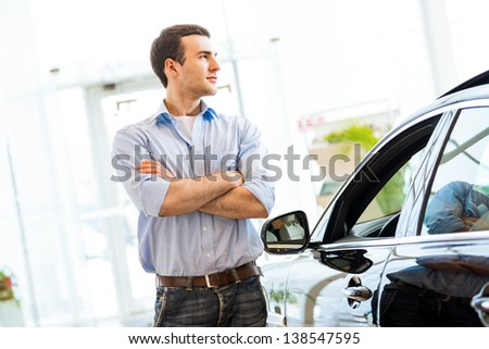 man standing near a car with his arms crossed, car showroom - stock photo