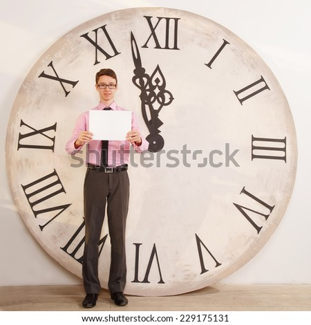 Man standing near the clock. Arrows show the big clock time. Male student or office worker. The clock at five minutes to twelve. Time of onset of the new year. Five minutes to midnight. Make a wish. - stock photo