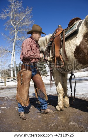 Man standing next to a horse while cinching up a saddle. Vertical shot. - stock photo