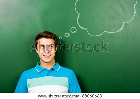 Man standing next to thought bubble on blackboard - stock photo