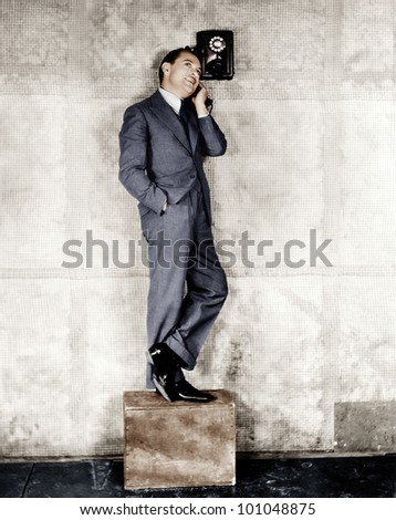 Man standing on a box to reach the telephone - stock photo