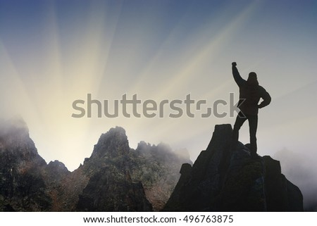 Man standing on a cliffs edge with raised hand against sunrise above Titnuldi mountain. Caucasus, Georgia, Svaneti.
