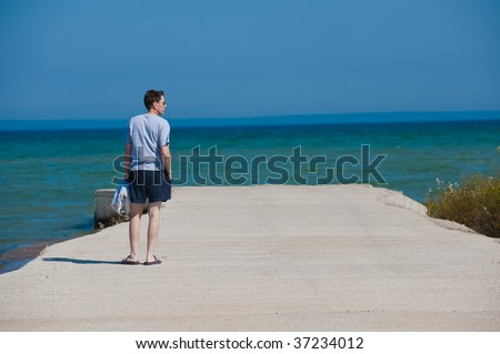 Man standing on a concrete pier, looking out on the water of Lake Huron in Michigan.