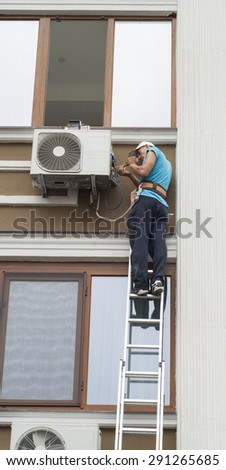 man standing on a ladder and sets the air conditioner outdoor unit - stock photo