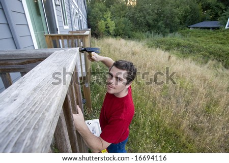 Man standing on a ladder hammering a porch. Horizontally framed photo. - stock photo