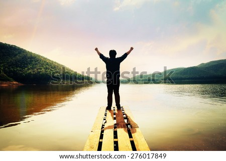 Man standing on a lake - stock photo