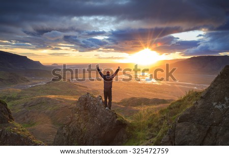 Man standing on a ledge of a mountain, enjoying the beautiful sunset over a wide river valley in Thorsmork, Iceland. - stock photo