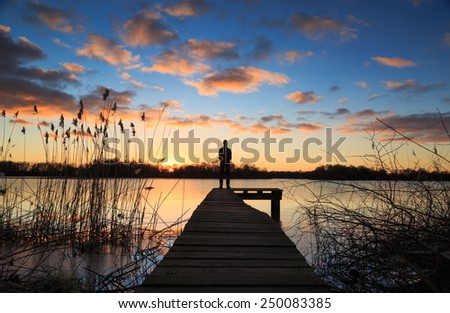 Man standing on a small jetty, enjoying the winter sunset over a lake. - stock photo