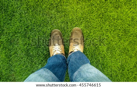 Man standing on a spring meadow,View of legs,Man with leather shoes enjoying beautiful green grass. - stock photo
