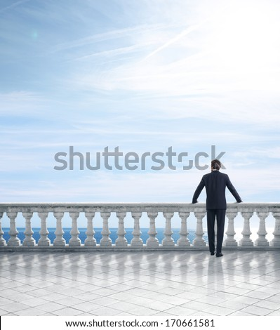 Man standing on a terrace overlooking the sea - stock photo
