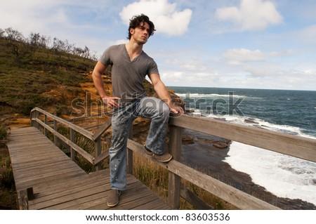 Man standing on a walk way overlooking the ocean - stock photo