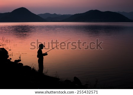 Man standing on fishing are  silhouette. Country life is beautiful. - stock photo