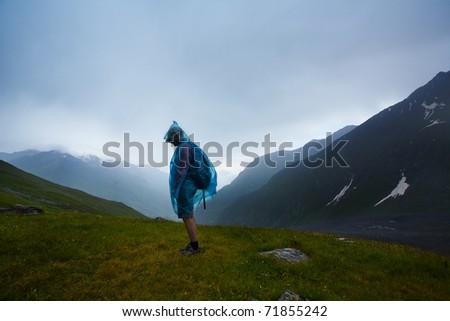 Man standing on green grass under heavy rain - stock photo