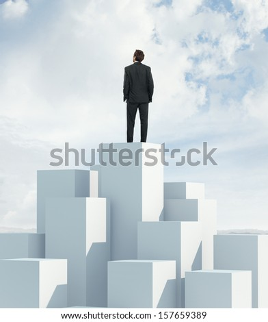 Man standing on highest cube and looking at sky - stock photo