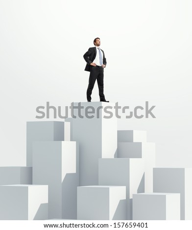 Man standing on highest cube. White background. - stock photo