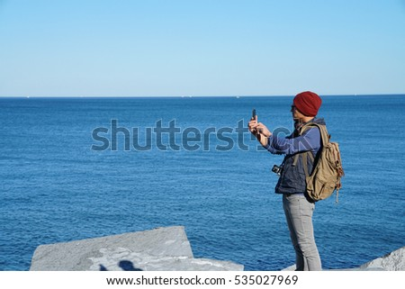 Man standing on rocks by the sea, taking pictures