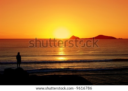 Man standing on rocks looking at the beautiful sunset