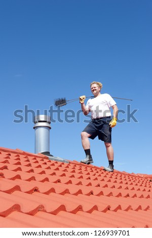 Man standing on rooftop of residential building to clean metal chimney of house with sweeper, with red roof and blue sky as background and copy space. - stock photo