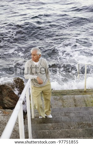 Man standing on stairs by the sea - stock photo