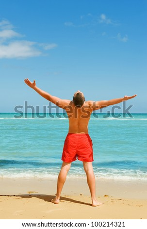 man standing on the beach spreading his hands - stock photo