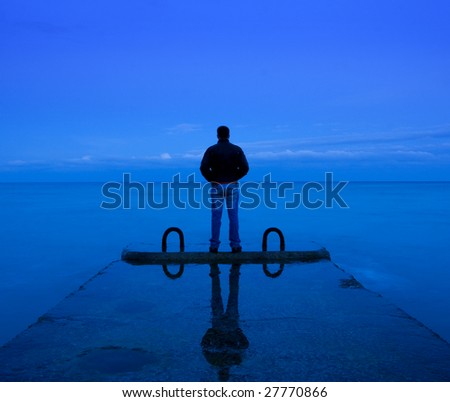 man standing on the concrete pier near the sea - stock photo