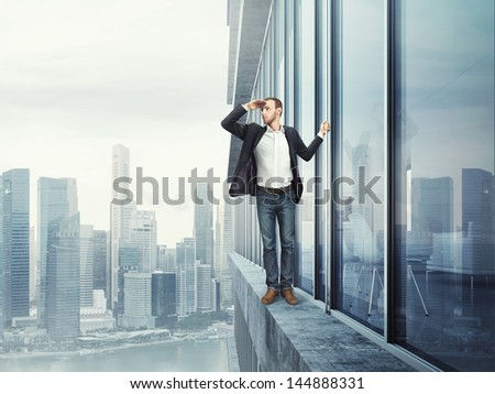 man standing on the edge and looking at the city - stock photo
