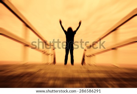 man standing on the edge of pier with hand open ,freedom concept,inspiration and joy - stock photo