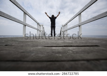 man standing on the edge of pier with hand open ,freedom concept,inspiration and joy,Successful Man - stock photo
