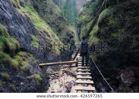 Man standing on the path through rocky canyon - stock photo