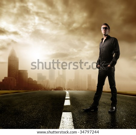 man standing on the road with a city on the background