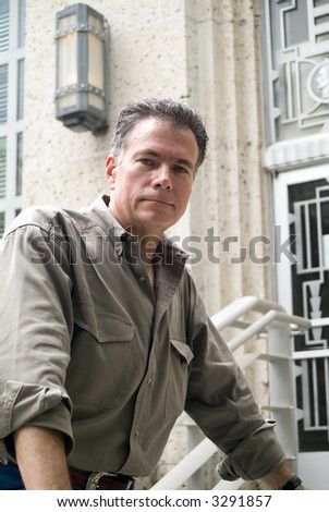Man standing on the steps of a building with an ornate metal and glass door in the background. - stock photo