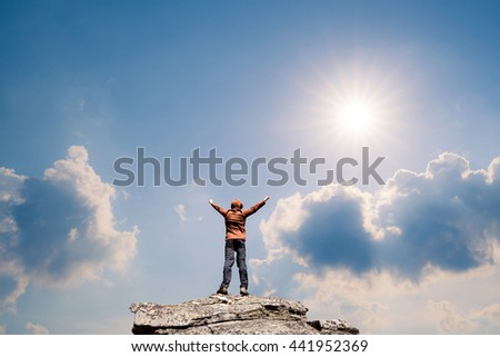 Man standing on the top of the mountain over blue and sunny sky - stock photo