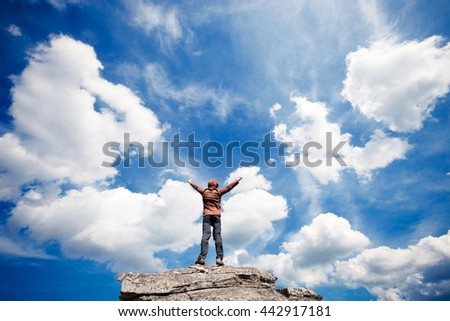 Man standing on the top of the mountain over blue sky