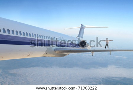 Man standing on the wing of an airplane - stock photo