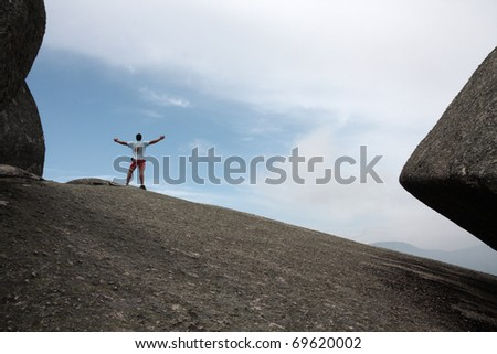 Man standing on top of a cliff - stock photo