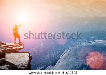Man standing on top of a cliff with arm raised - stock photo