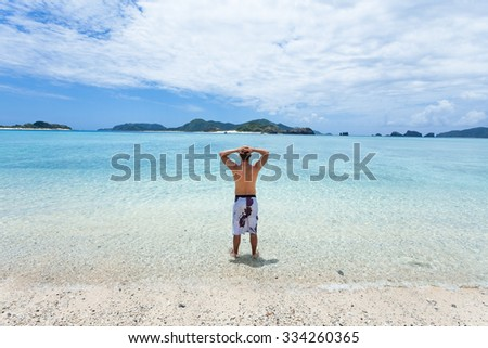 Man standing on tropical beach, looking at deserted coral islands on the horizon, Zamami Island of the Kerama Islands National Park, Okinawa, Japan - stock photo