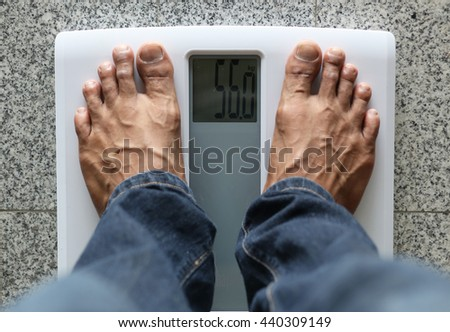 Man standing on weight scale - stock photo