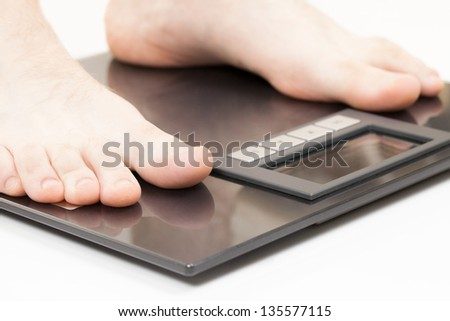 Man standing on weight scales with bare foot - stock photo