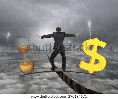 Man standing on wood board between hourglass and golden dollar sign, balancing on wire, with stormy mist cityscape background. Time is money concept. - stock photo