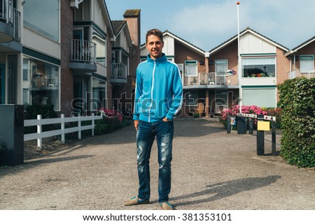 man standing outside houses in day time