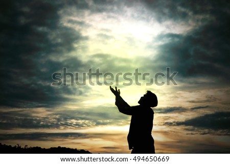 Man standing prays for god in nature morning light