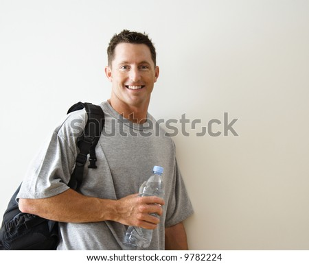 Man standing smiling with gym bag and bottled water. - stock photo