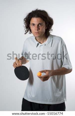 Man standing up holding a ping pong ball and a paddle. He has a serious expression on his face. Vertically framed photograph - stock photo