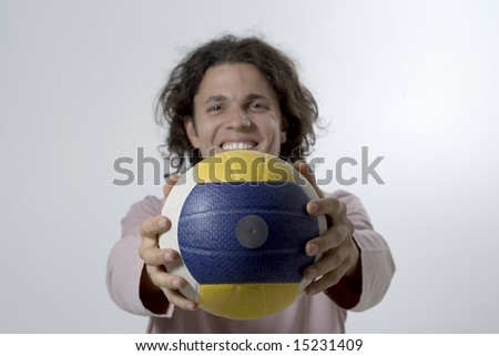 Man standing up holding a volleyball out in front of him and smiling at the camera.  Horizontally framed photo. - stock photo