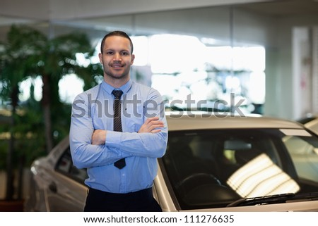 Man standing while crossing his arms in a dealership - stock photo