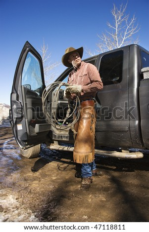 Man standing with a lariat next to the open door of a pickup truck. Vertical shot. - stock photo