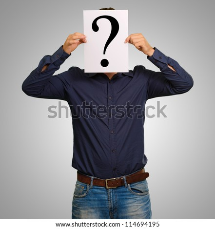 Man standing with a question mark board isolated on gray background - stock photo