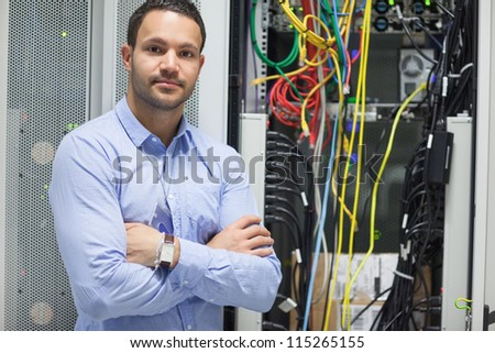 Man standing with arms crossed in data center in front of servers