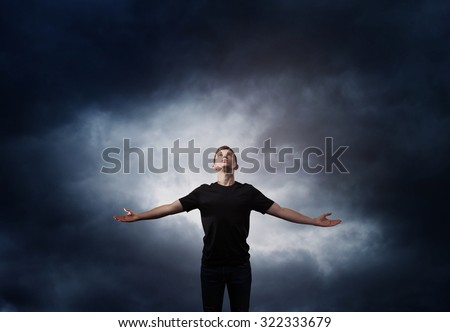Man standing with arms wide open over dark sky - stock photo